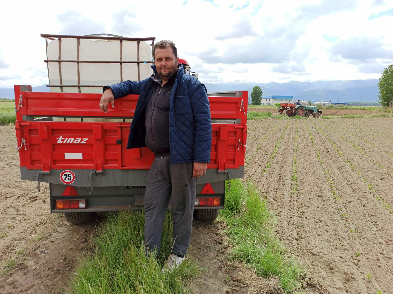 A farmer standing in front of a vehicle on a field